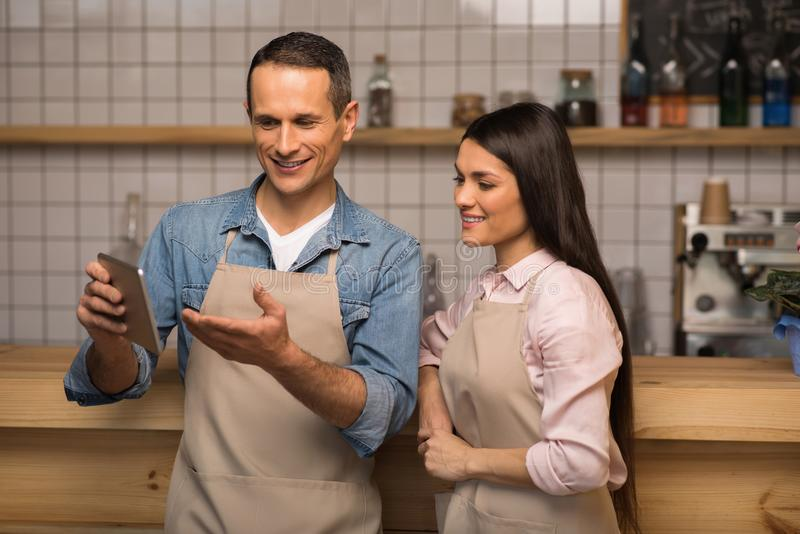 Cafe owner showing something to waitress on digital tablet. Smiling cafe owner showing something to waitress on digital tablet in coffee shop stock images