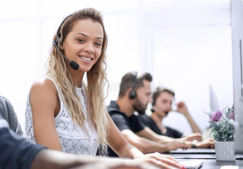 Smiling call center employee sitting at his Desk. Photo with text space stock photography