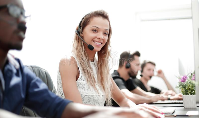 Smiling call center employee sitting at his Desk. Photo with text space royalty free stock images