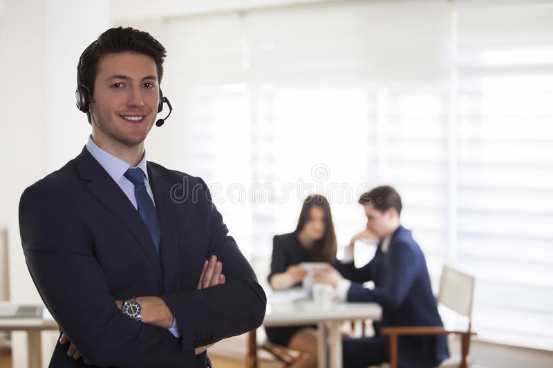 Smiling call center employee during a telephone conversation stock image
