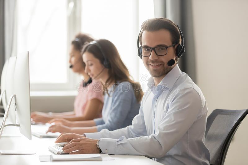 Smiling call center worker sitting at workplace looking at camera stock photo