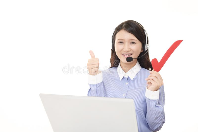 Smiling call center operator with a check mark. Portrait of a call center operator stock photo