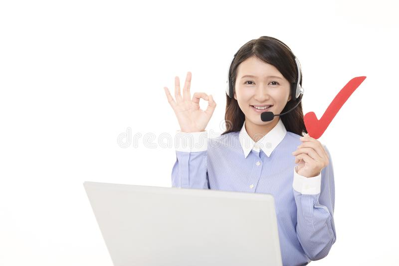 Smiling call center operator with a check mark. Portrait of a call center operator stock image