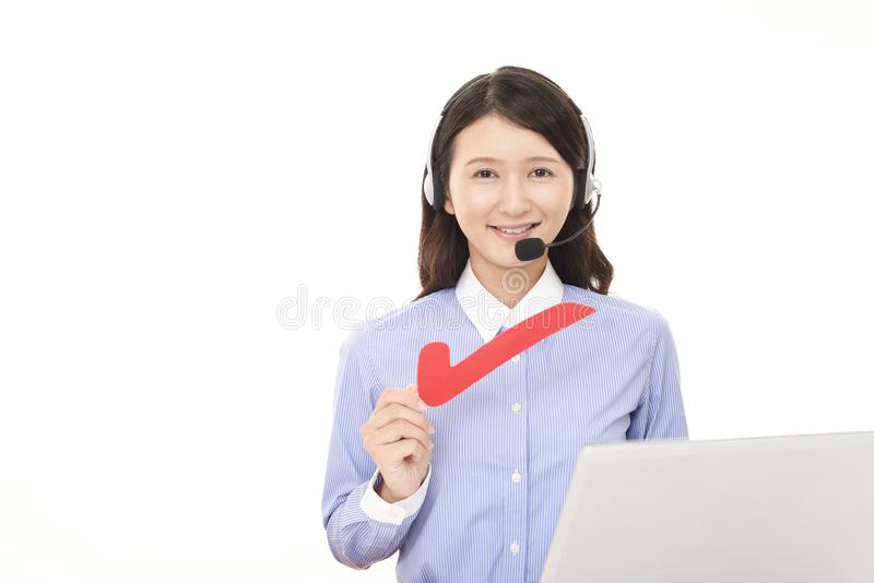 Smiling call center operator with a check mark. Portrait of a call center operator royalty free stock photography