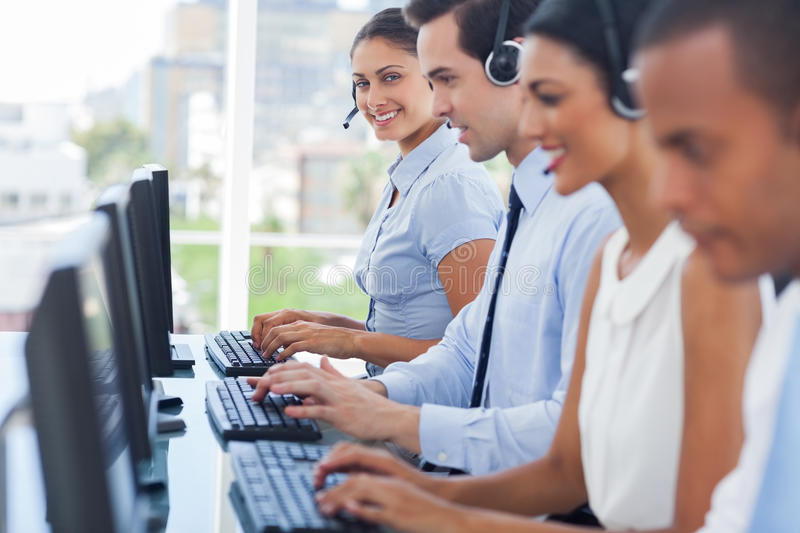 Smiling call centre employees working on computers. With their headsets royalty free stock photo