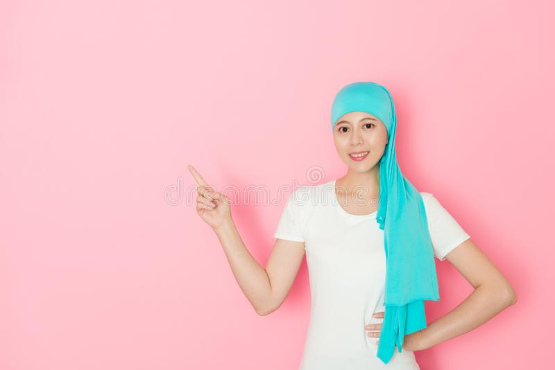Smiling cancer patient standing in pink background royalty free stock photos