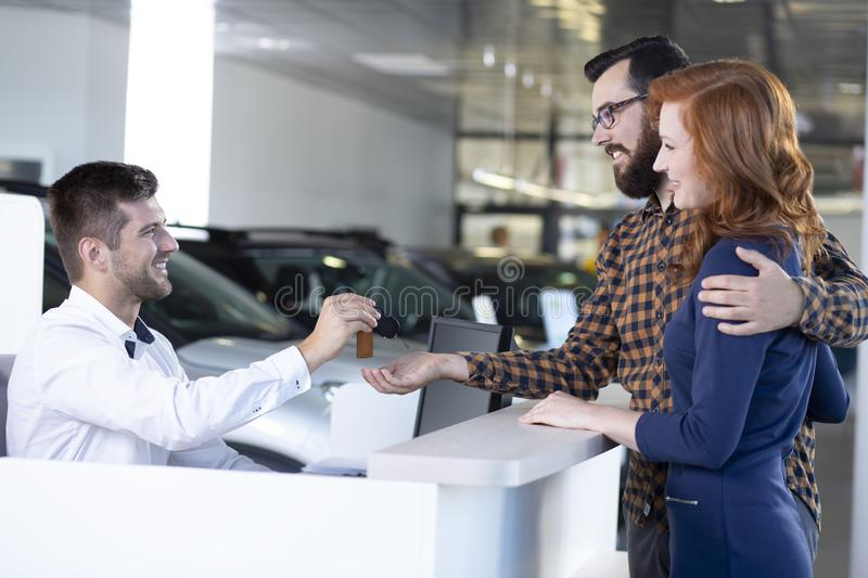 Smiling car dealer giving keys to happy marriage after transaction in a dealing salon royalty free stock image