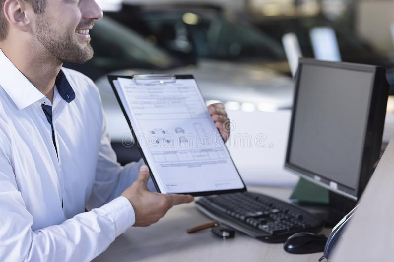 Smiling car dealer showing daily agreement and receipt to buyer during transaction stock image