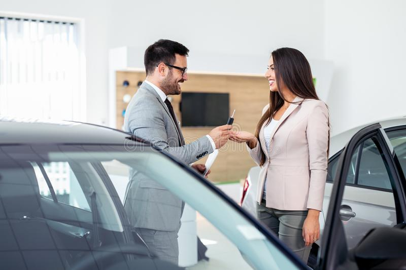 Smiling car salesman handing over your new car keys. Happy girl the buyer. royalty free stock image