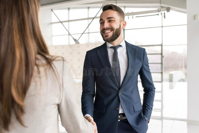 Smiling Car Salesman Shaking Hands with Client. Portrait of smiling car salesman shaking hands with women buying new car in dealership showroom royalty free stock image