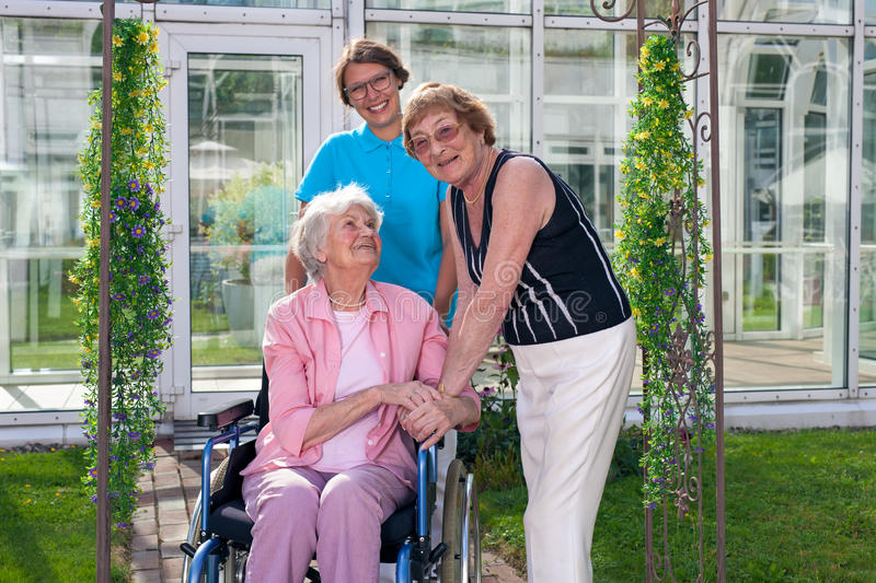 Smiling Care Takers for Old Patient on Wheel Chair. Two Smiling Care Takers, Looking at Camera, for Old Age Patient on Wheel Chair. Captured at Grassy Green stock photo