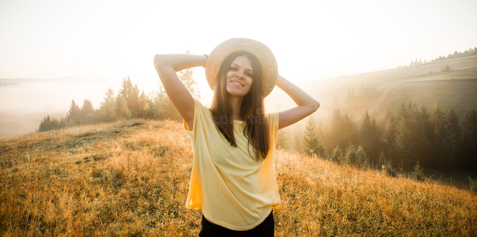 Smiling carefree woman with open arms to sunrise stand on top of hill royalty free stock photos
