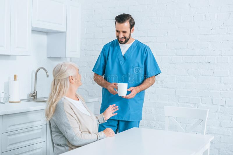 Smiling caregiver holding cup and looking at senior woman. Sitting in kitchen stock image