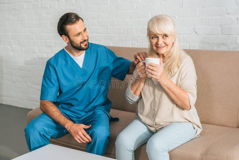 Smiling caregiver looking at happy senior woman. Drinking tea stock photos