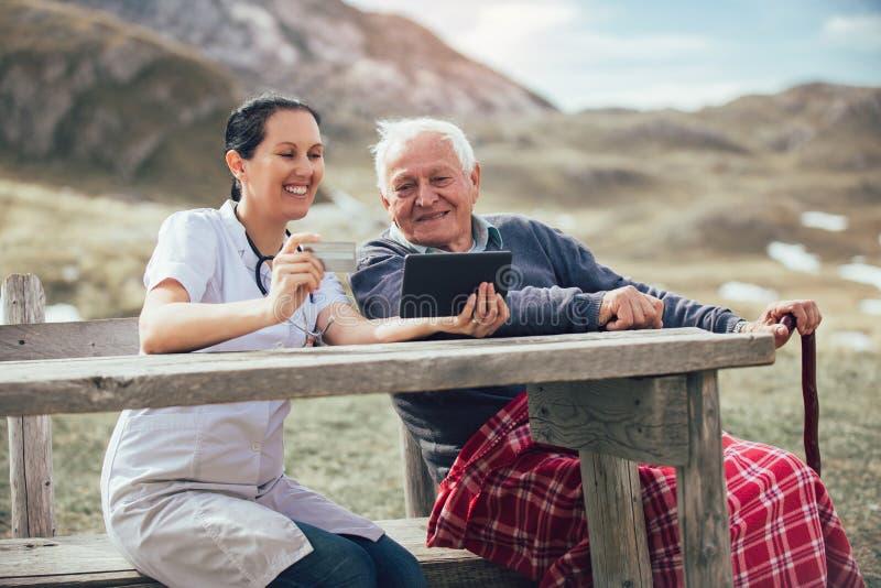 Smiling caregiver nurse and disabled senior patient using digital tablet stock photo
