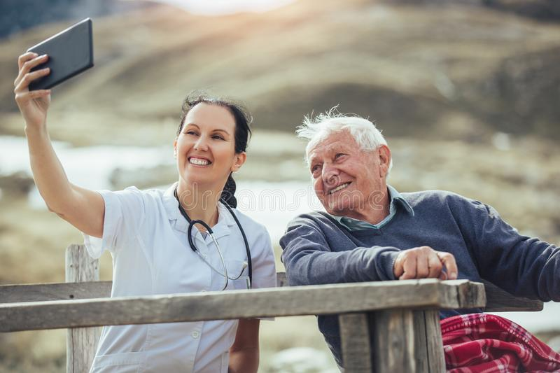 Smiling caregiver nurse and senior patient using digital tablet. Smiling caregiver nurse and disabled senior patient using digital tablet outdoor royalty free stock photo