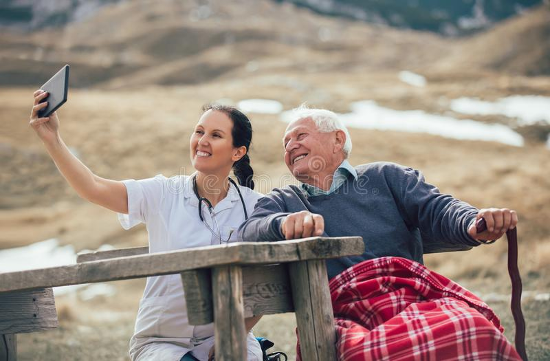 Smiling caregiver nurse and disabled senior patient using digital tablet. Outdoor stock photo