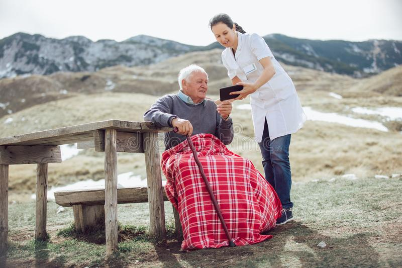 Smiling caregiver nurse and disabled senior patient using digital tablet. Outdoor royalty free stock photography