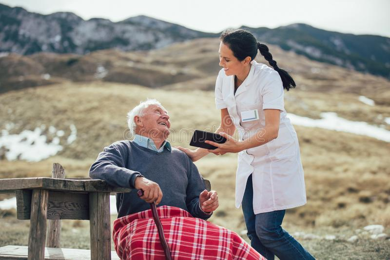 Smiling caregiver nurse and senior patient using digital tablet. Smiling caregiver nurse and disabled senior patient using digital tablet outdoor royalty free stock photos