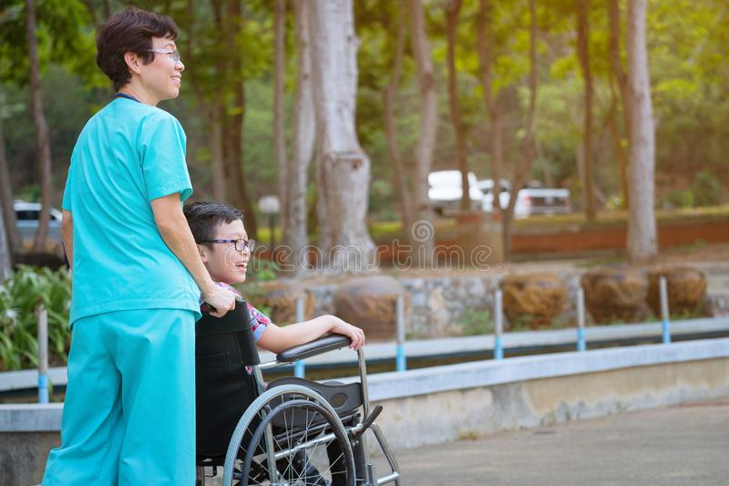 Smiling caregiver Senior nurse take care a boy patient in wheelchair for relaxing and looking around park stock photos