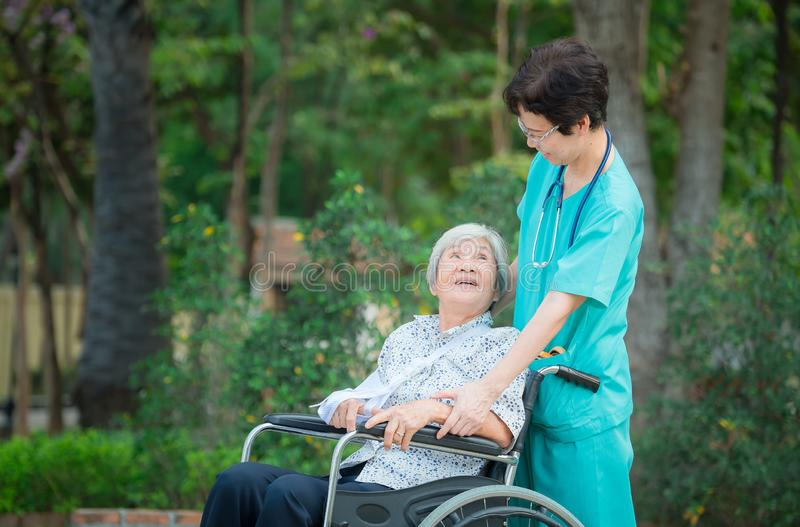 Smiling caregiver Senior nurse take care a Senior patient on wheelchair for relaxing and looking around park stock photos