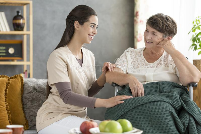 Smiling caregiver and senior woman. Smiling caregiver and disabled senior women spending time together in a hospice stock photography