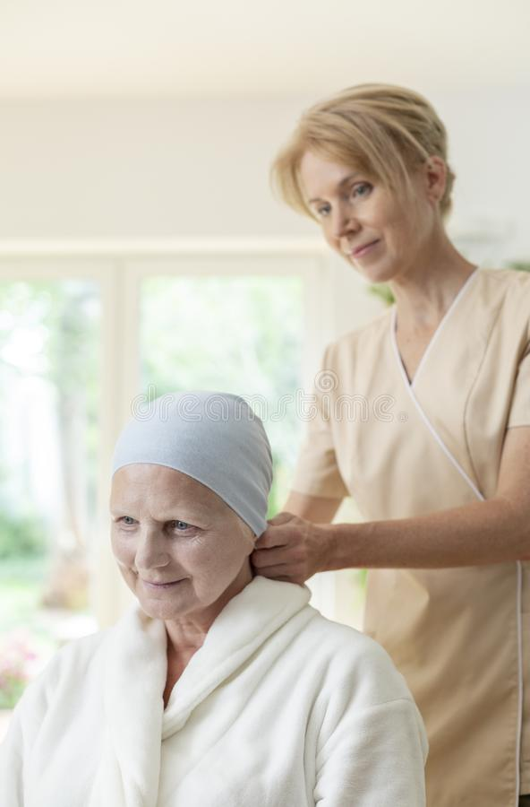 Smiling caregiver and sick elderly woman with cancer stock photography