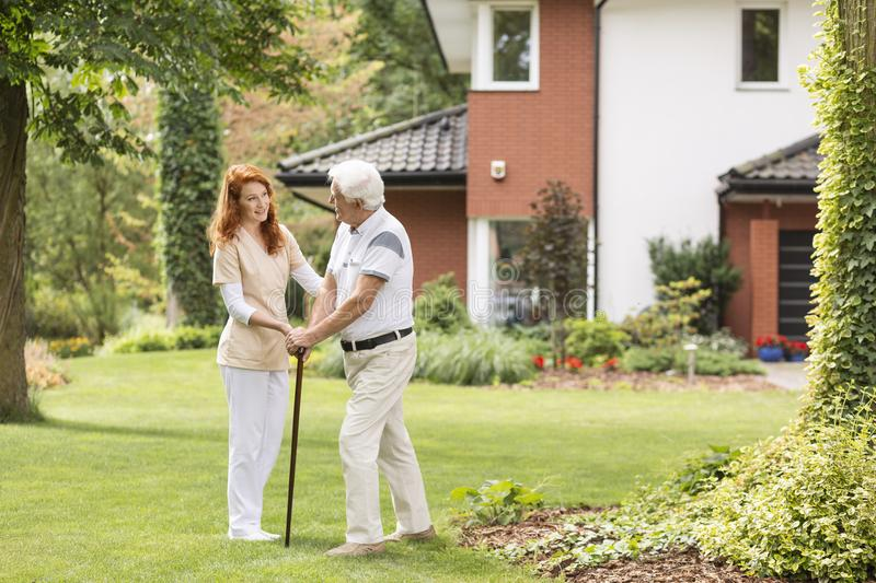 Smiling caregiver supporting senior man with walking stick in th. Smiling caregiver supporting senior men with walking stick in the garden royalty free stock image