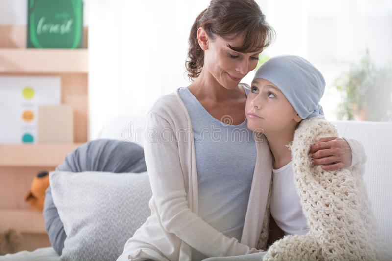 Smiling caregiver supporting sick child with cancer wearing blue headscarf royalty free stock images