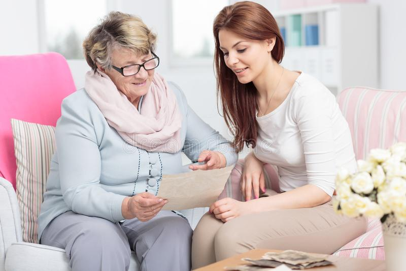 Caregiver watching photos while visiting happy elderly woman at home. Smiling caregiver watching photos while visiting happy elderly women at home stock image