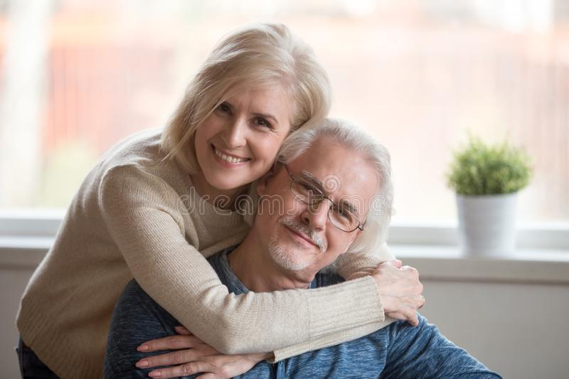 Smiling caring middle aged wife embracing senior husband, portra stock image