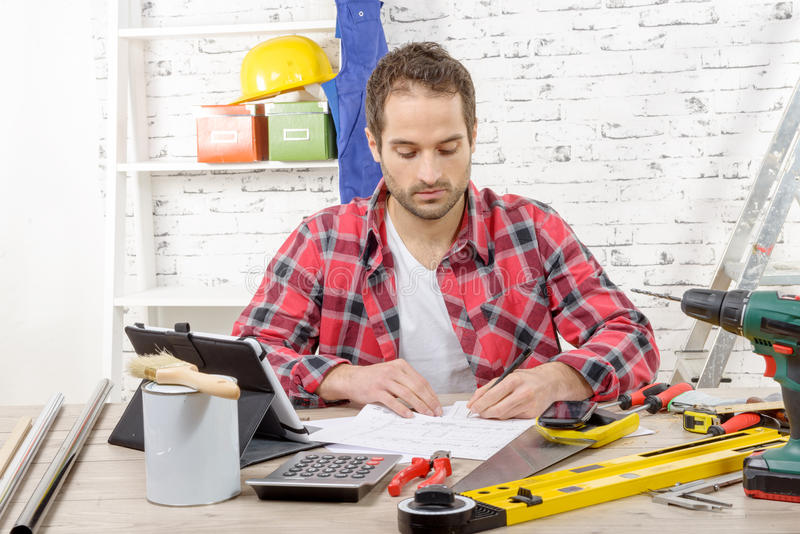 Smiling carpenter sitting at the desk, in his studio royalty free stock images