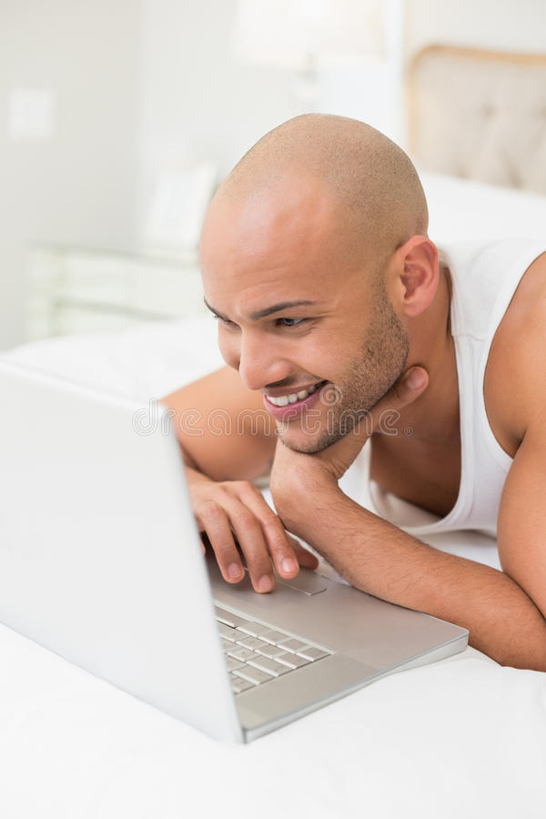 Smiling casual bald man using laptop in bed. Close up of a smiling casual bald young man using laptop in bed at home stock photos