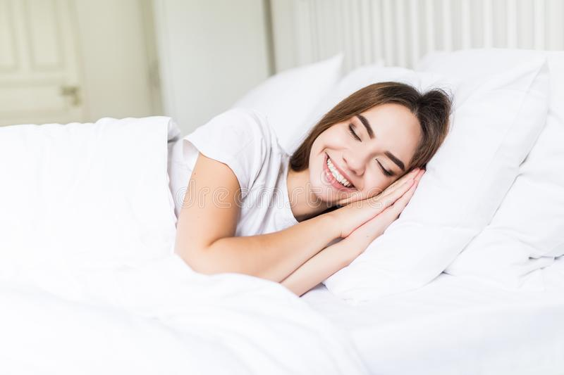 Smiling casual brunette lying in her bed in bright bedroom before sleep. Smiling casual brunette lying in her bed in bright bedroom stock photo