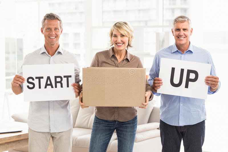 Smiling casual business people holding start up sign stock image