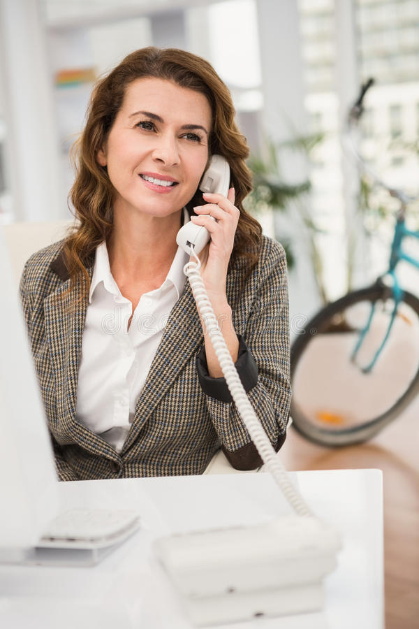 Smiling casual businesswoman phoning stock images