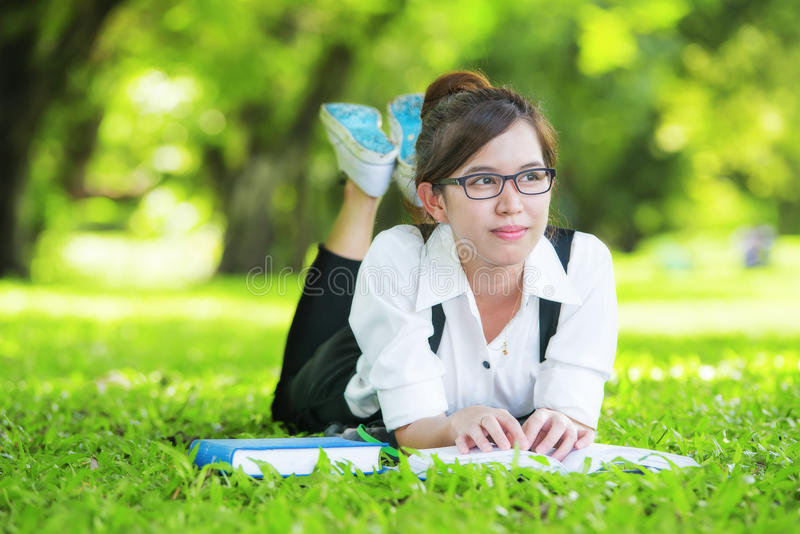 Smiling casual student lying on grass reading book royalty free stock photos