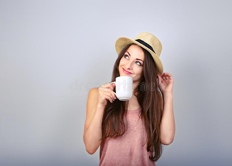 Smiling casual thinking woman with cup of coffee looking up in straw hat on blue background with empty copy space Closeup royalty free stock photos
