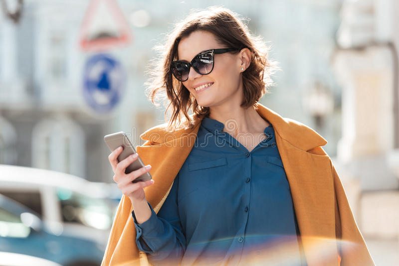 Smiling casual woman in sunglasses looking at mobile phone royalty free stock photos