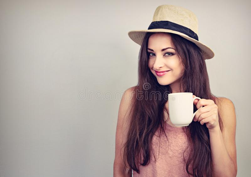 Smiling casual young woman with cup of coffee looking happy in straw hat on blue background stock images
