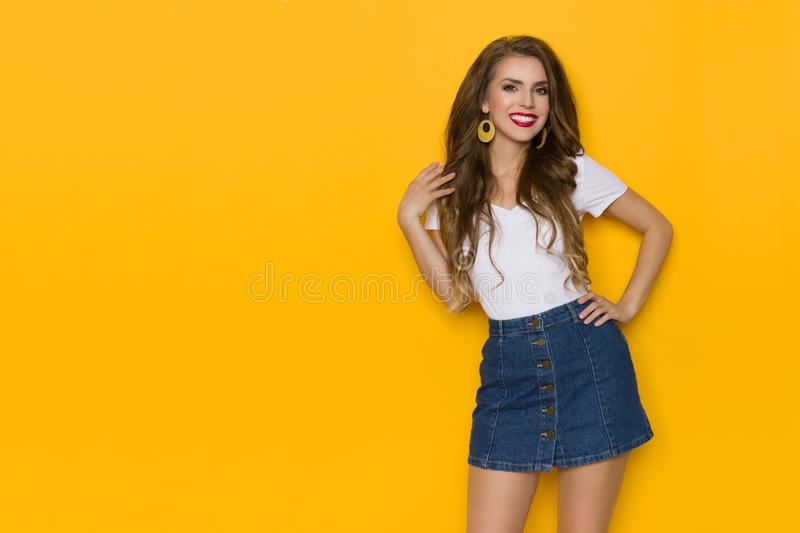 Smiling Casual Young Woman In Jeans Mini Skirt. Beautiful young woman in jeans mini skirt and white top is looking at camera, holding hand on hair and smiling royalty free stock image