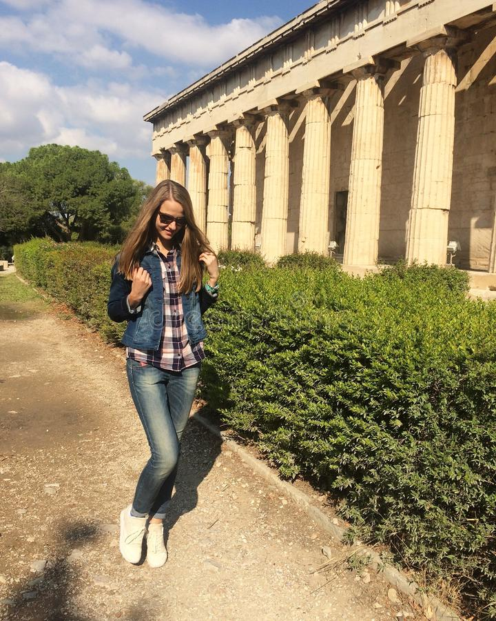 Smiling Caucasian girl in sunglasses. A girl with long hair in a denim suit and white sneakers the girl walking along the ancient stock images