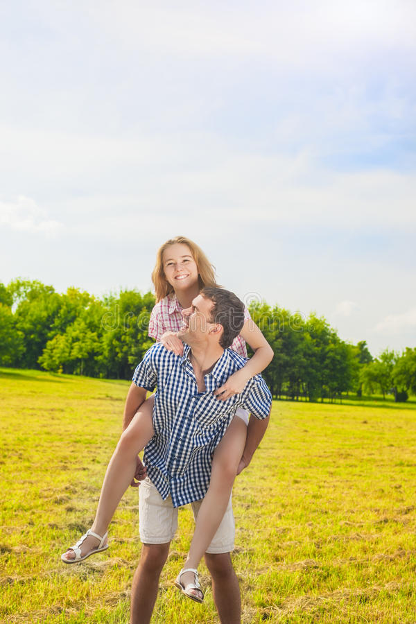 Smiling Caucasian Man Giving Woman Piggyback Ride Outdoors. Youth Lifestyle, Happiness, Love, dating, Romance , Vacation Concept. stock images