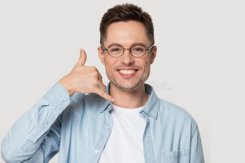 Smiling Caucasian man in glasses show call me gesture. Smiling Caucasian young man in glasses isolated on grey studio background show call me gesture looking at stock photo