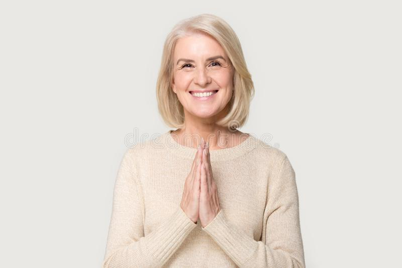 Smiling senior woman with hands in prayer look at camera stock photography