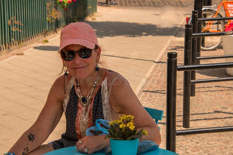 Smiling caucasian Woman baby boomer wearing a pink cap with dog paw tattoos on her right forearm is sitting at a blue table outdoo. Rs on the sidewalk in the royalty free stock images