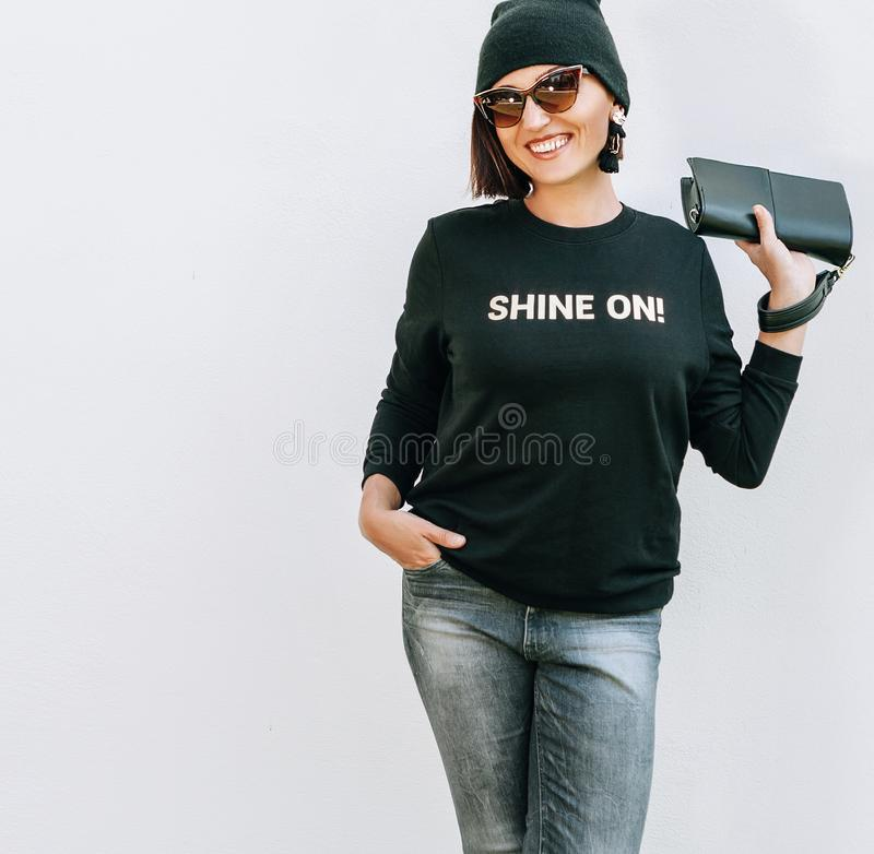 Smiling caucsaian woman in trendy casual grey black outfit for spring summer days. Sweatshirt with funny positive print stock images
