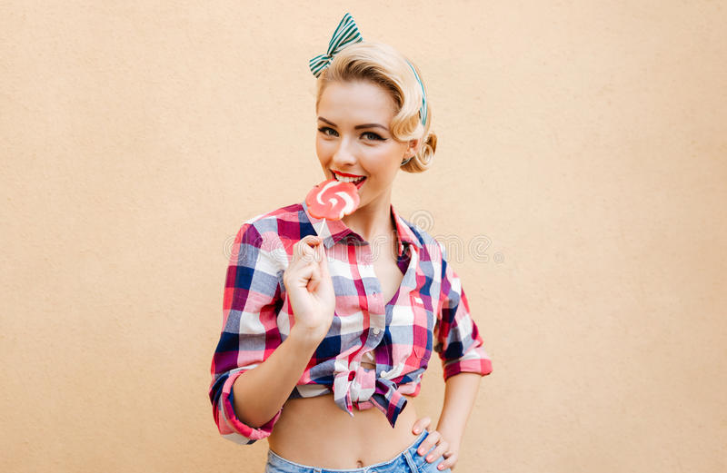 Smiling charming pin-up girl standing and eating sweet lollipop royalty free stock photography