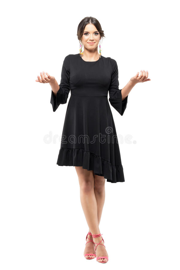 Smiling charming uncertain woman in black dress shrugging shoulders with raised arms. royalty free stock photography