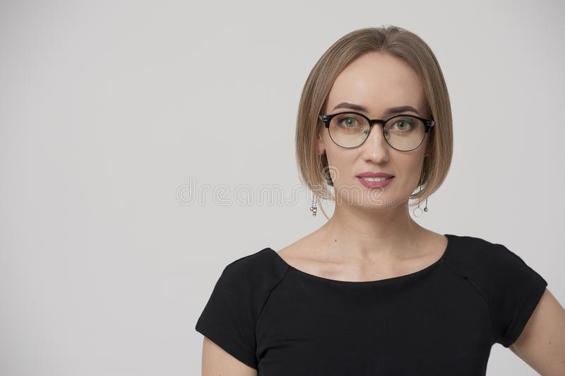 Smiling charming young businesswoman wearing formal suit and stylish glasses stock image